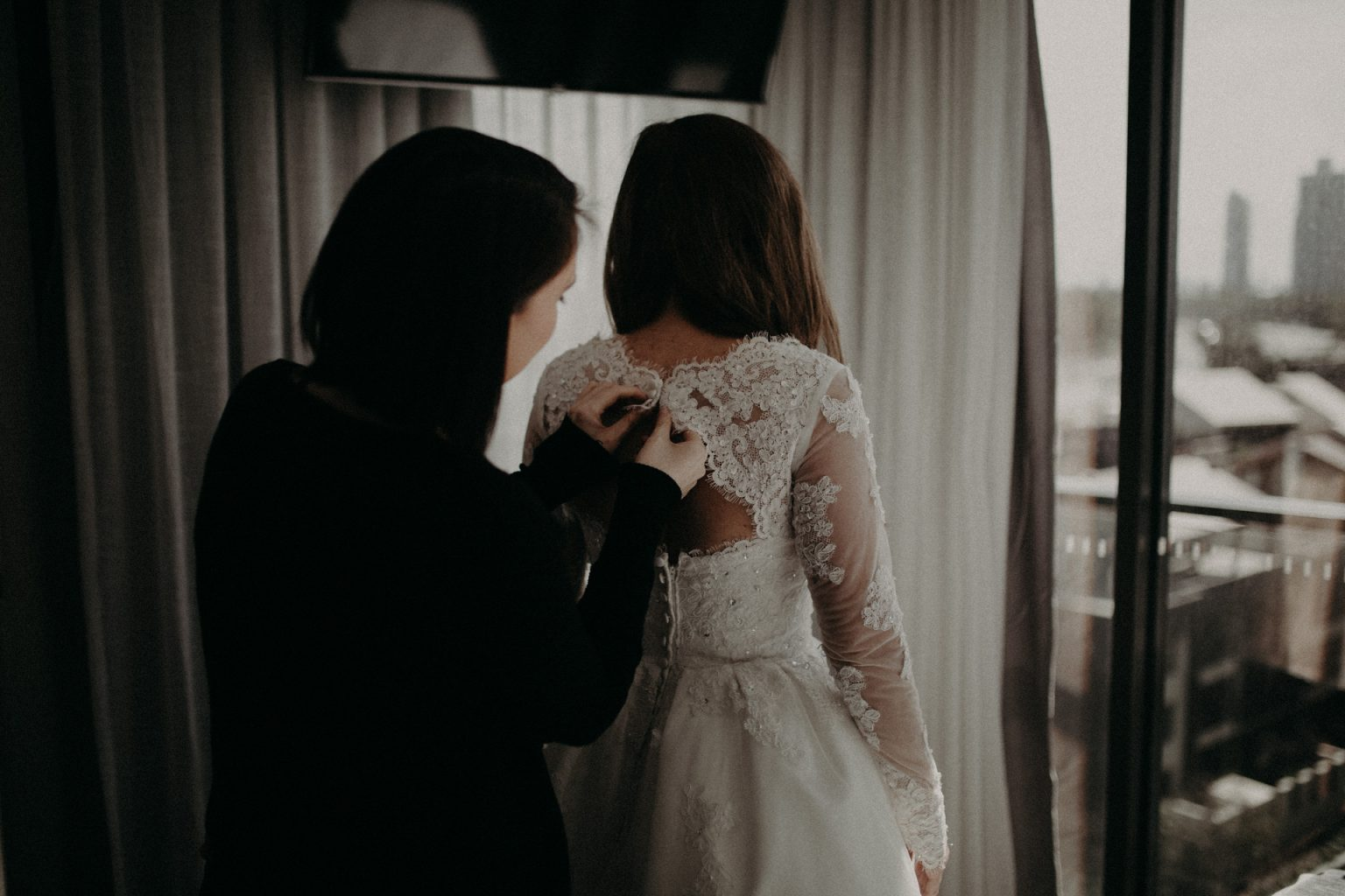 bridesmaid helping bride with gown