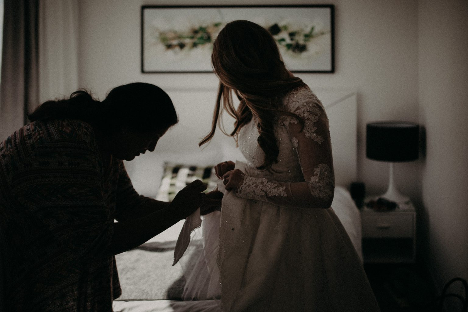 mother helping bride with dress