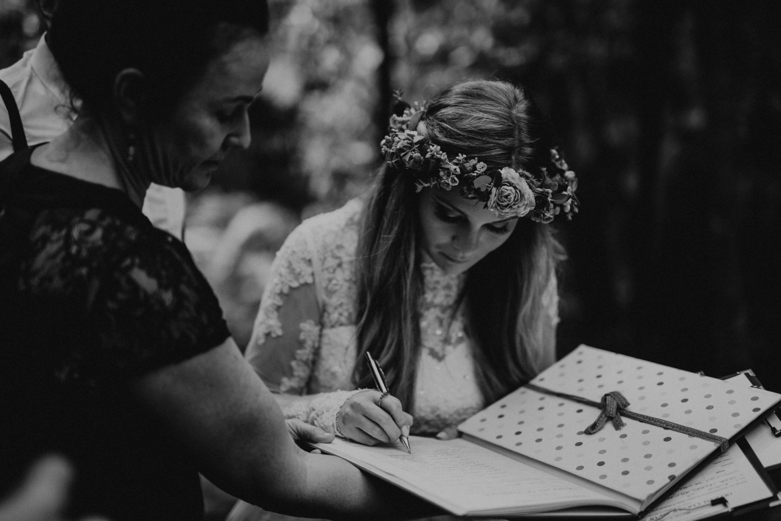 bride signing paperwork in forest