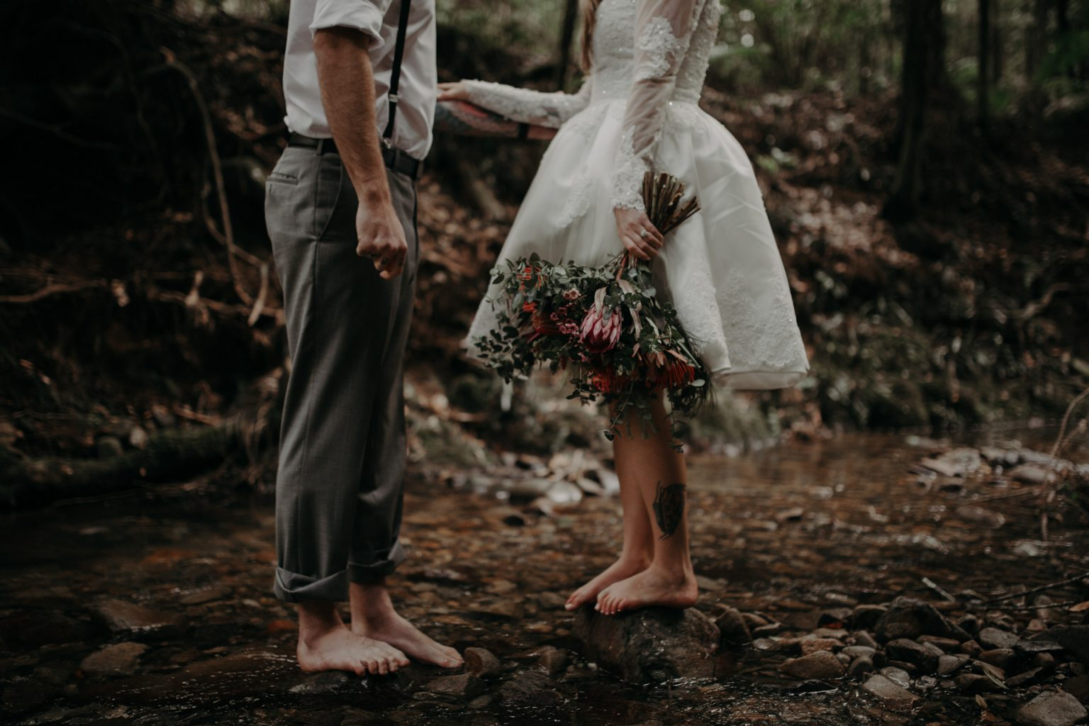 bride and groom walking in forest bouquet wildflowers