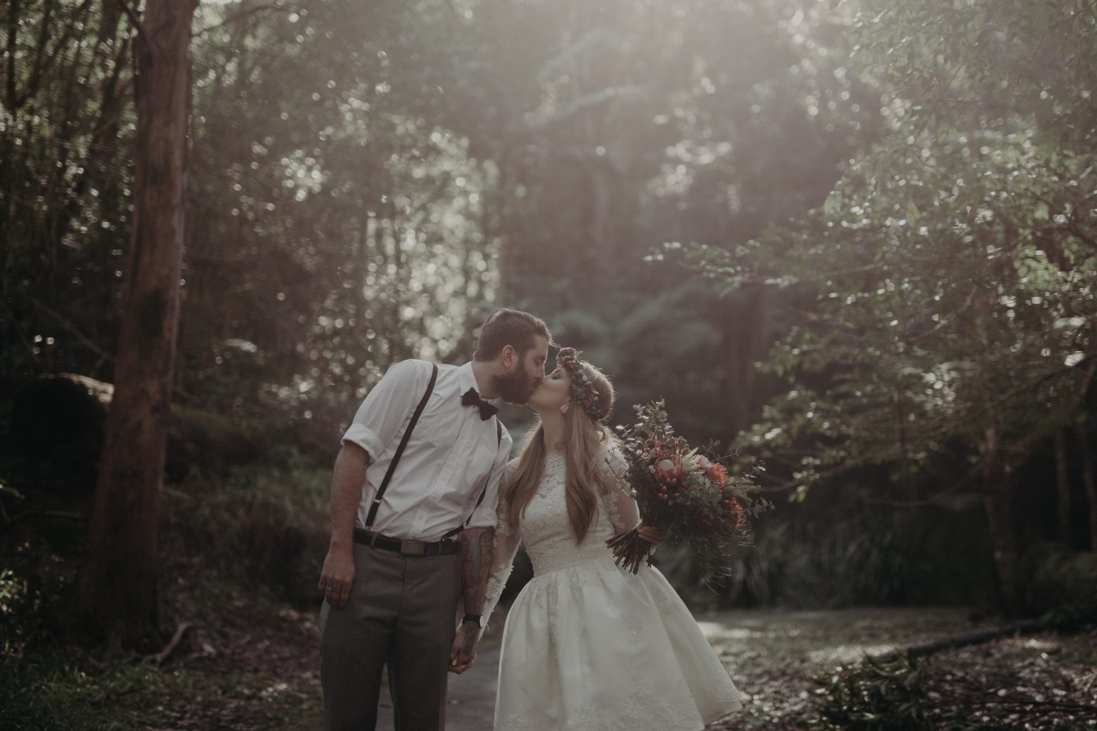 bride groom kissing on forest path