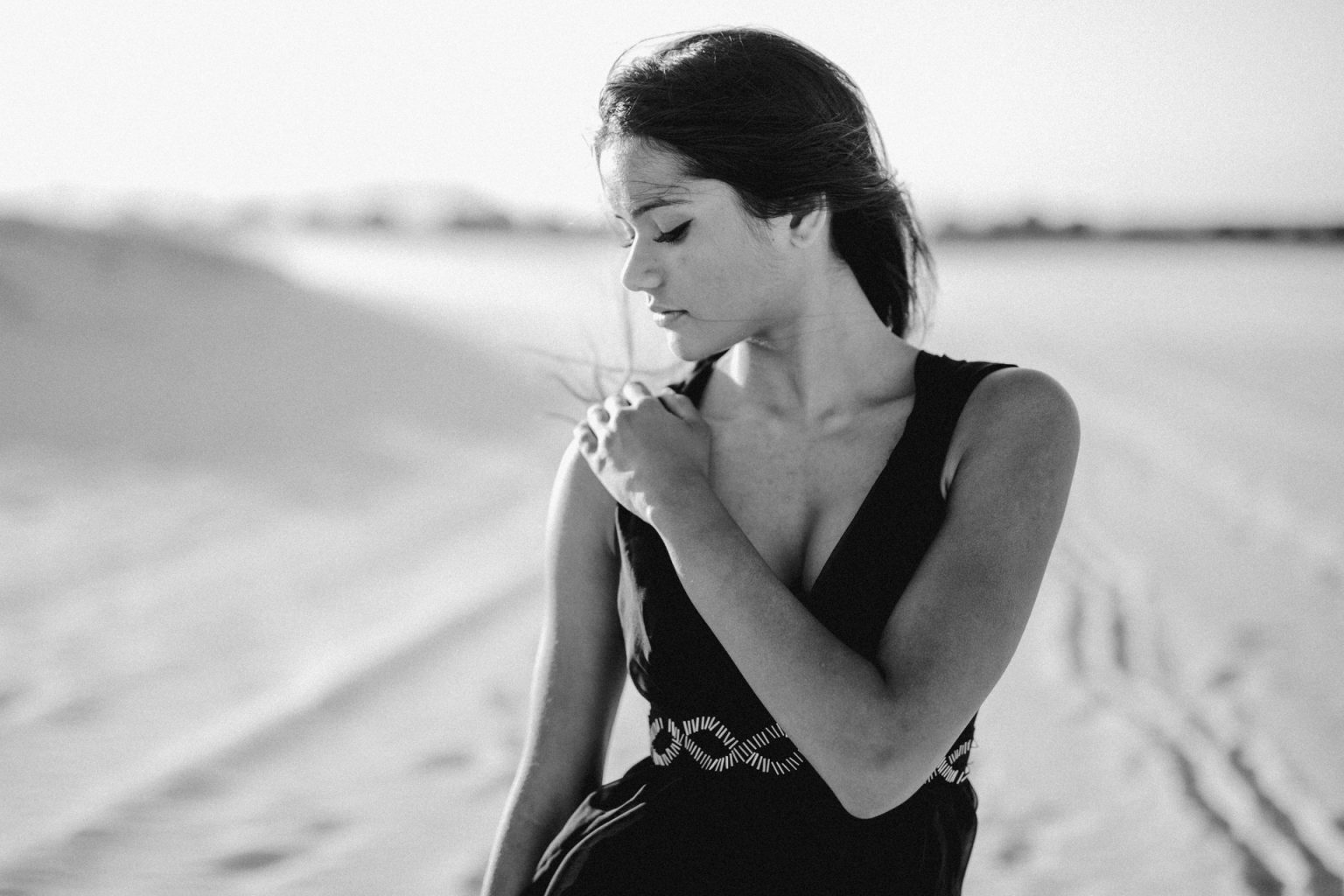 woman on beach windy hair brunette