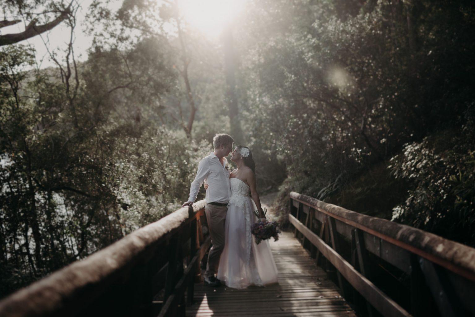 bride and groom walking through forest burleigh headland bridge