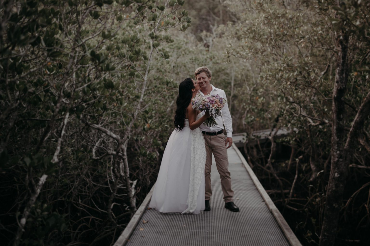 bride and groom walking through forest burleigh headland boardwalk