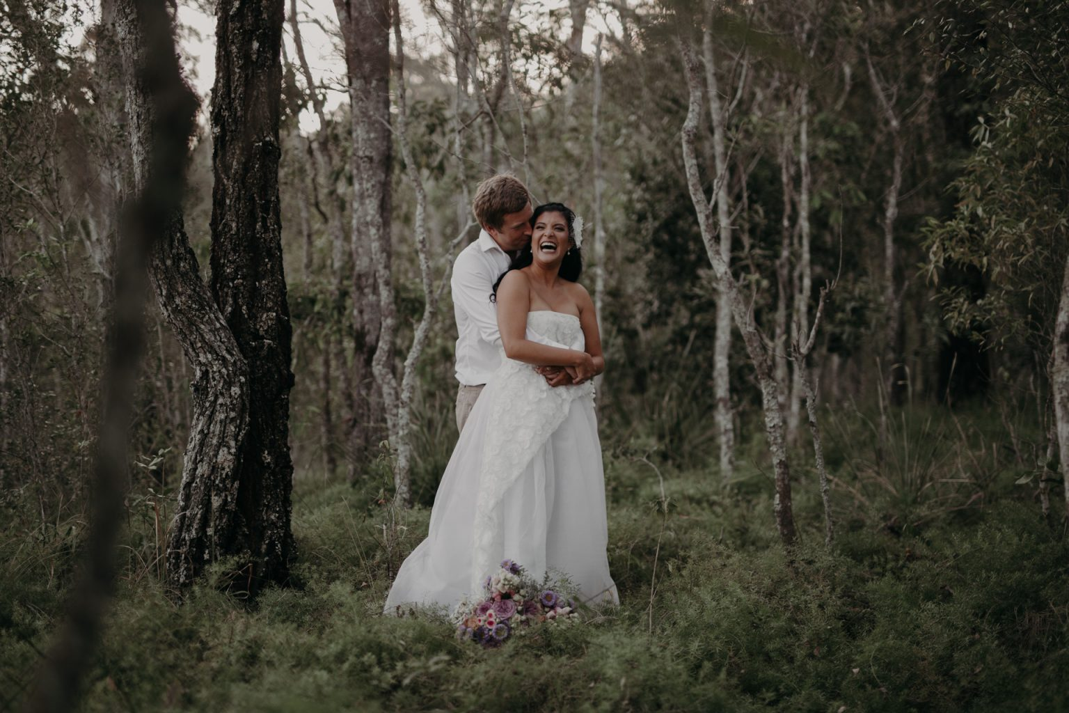 bride and groom walking through forest burleigh headland laughing