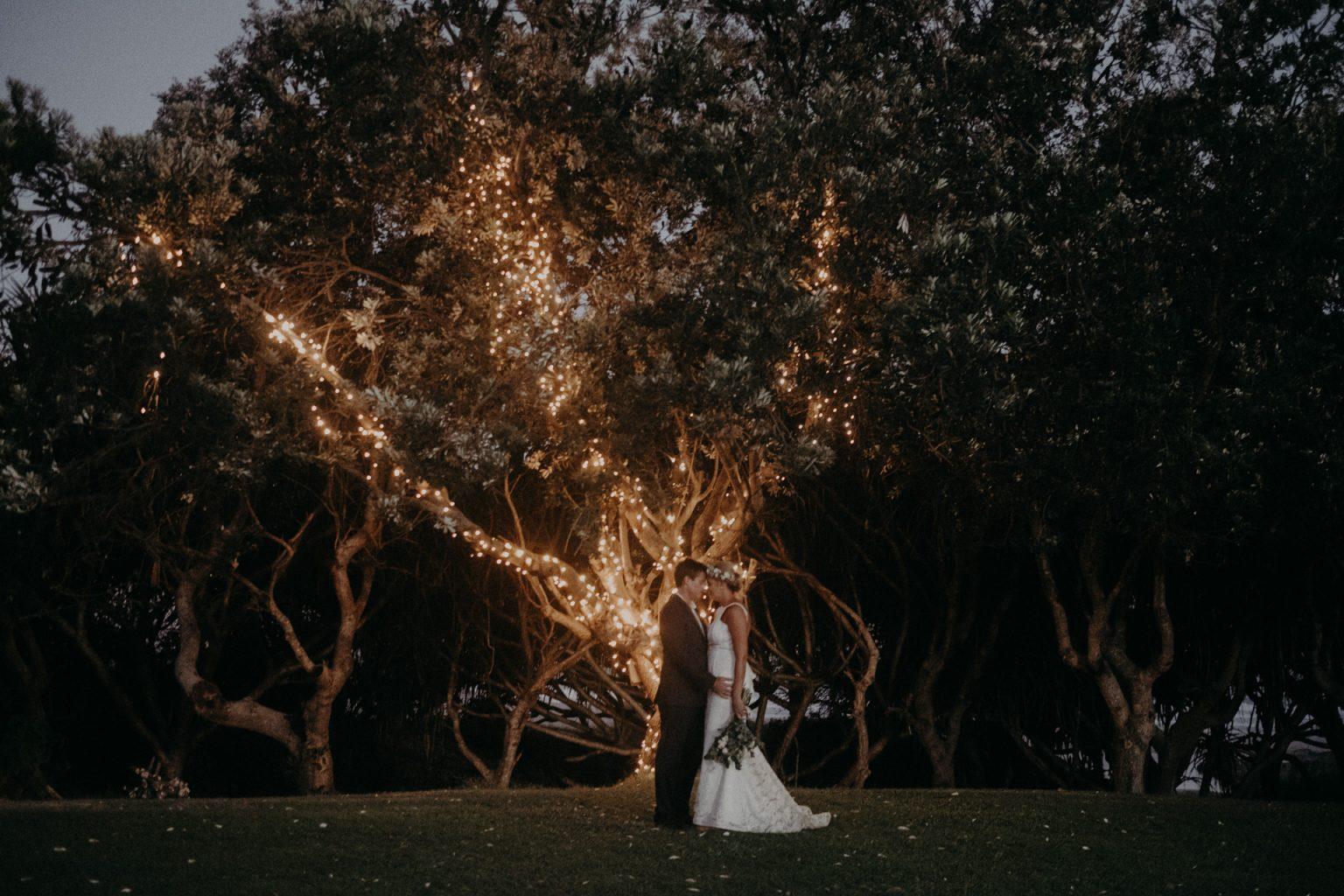 bride and groom cabaret beach long grass tree fairy lights
