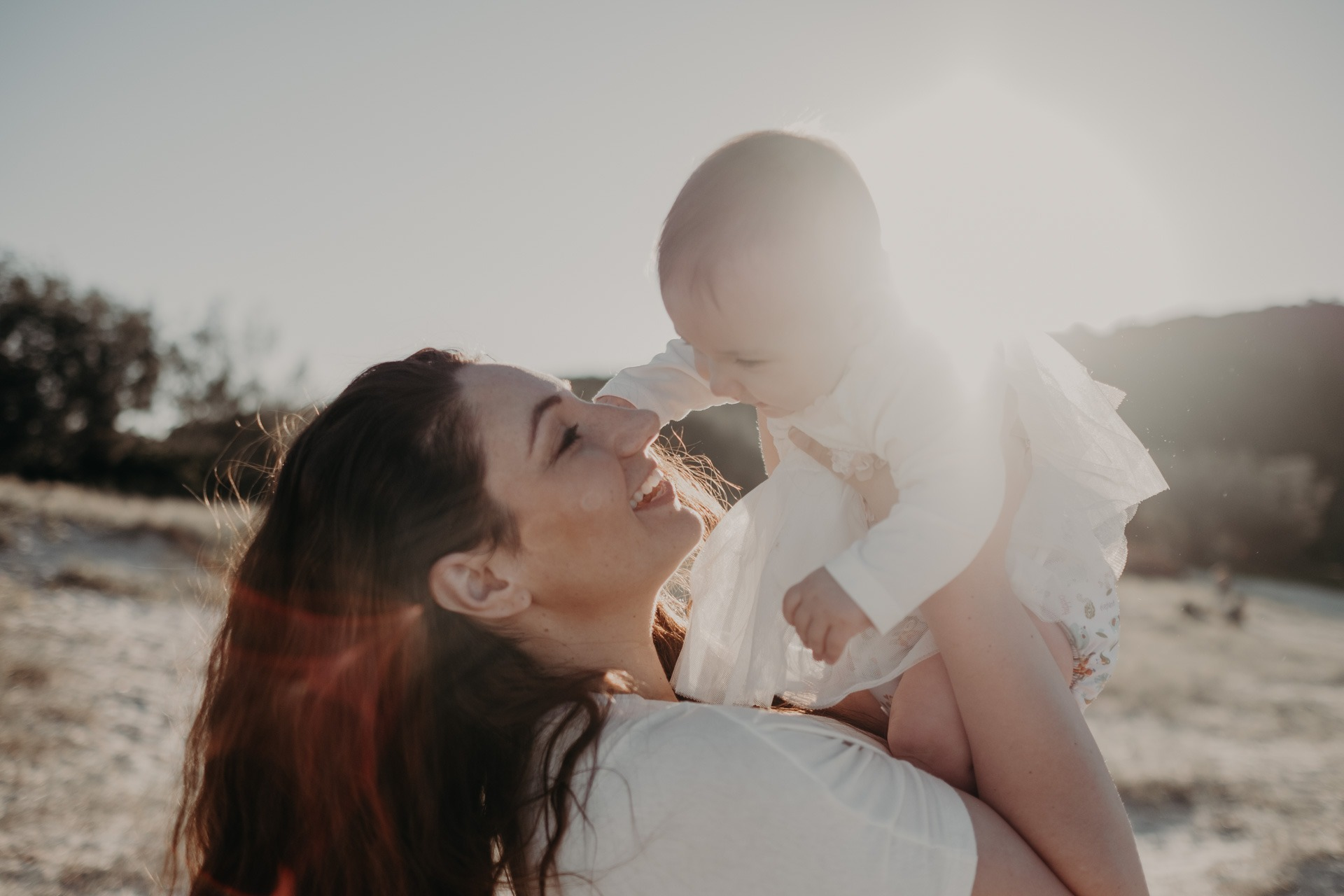mother and baby on beach Tallebudgera sun flare