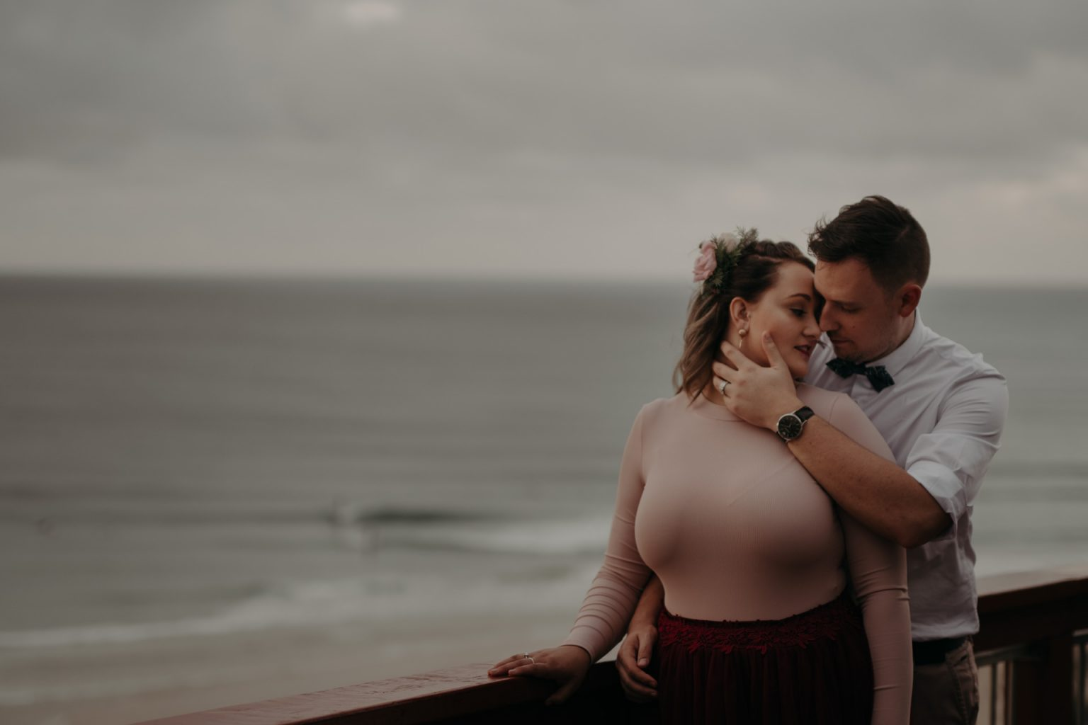 bride and groom on cliff storm clouds pink dress