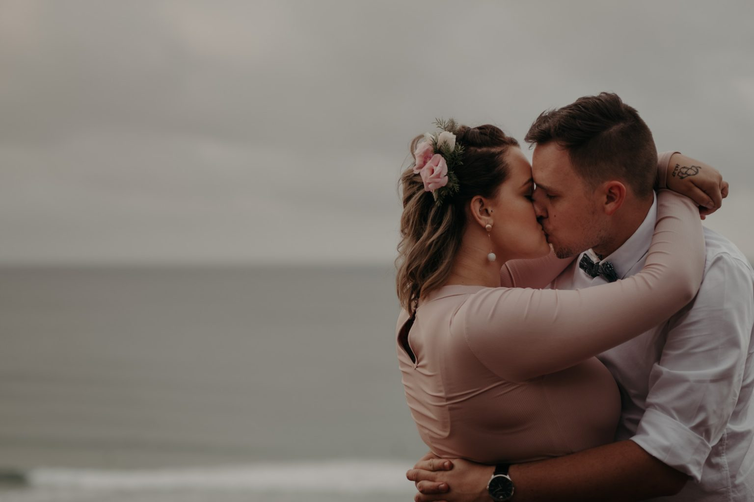bride and groom on cliff storm clouds pink dress kiss