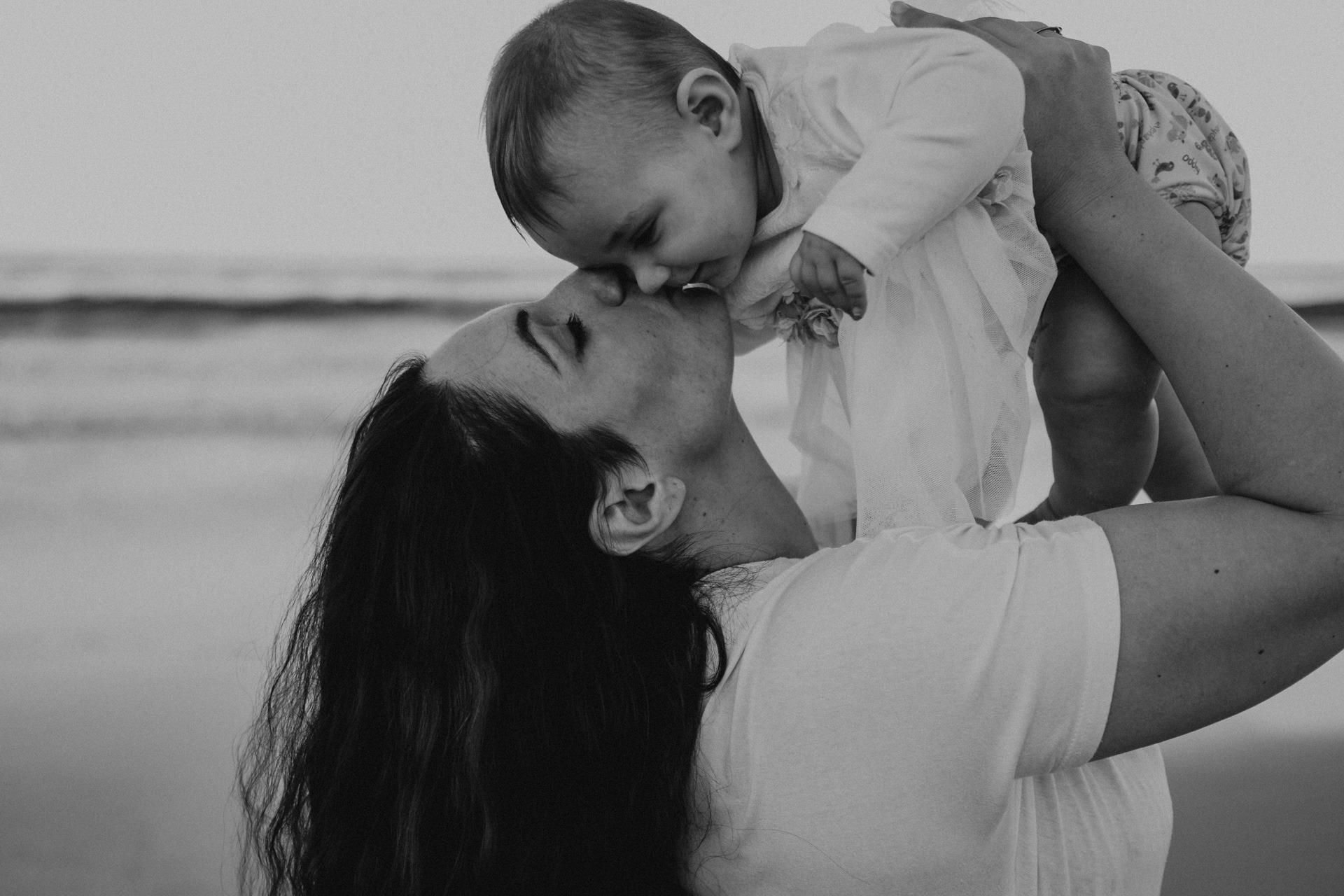 mother and baby on beach kiss