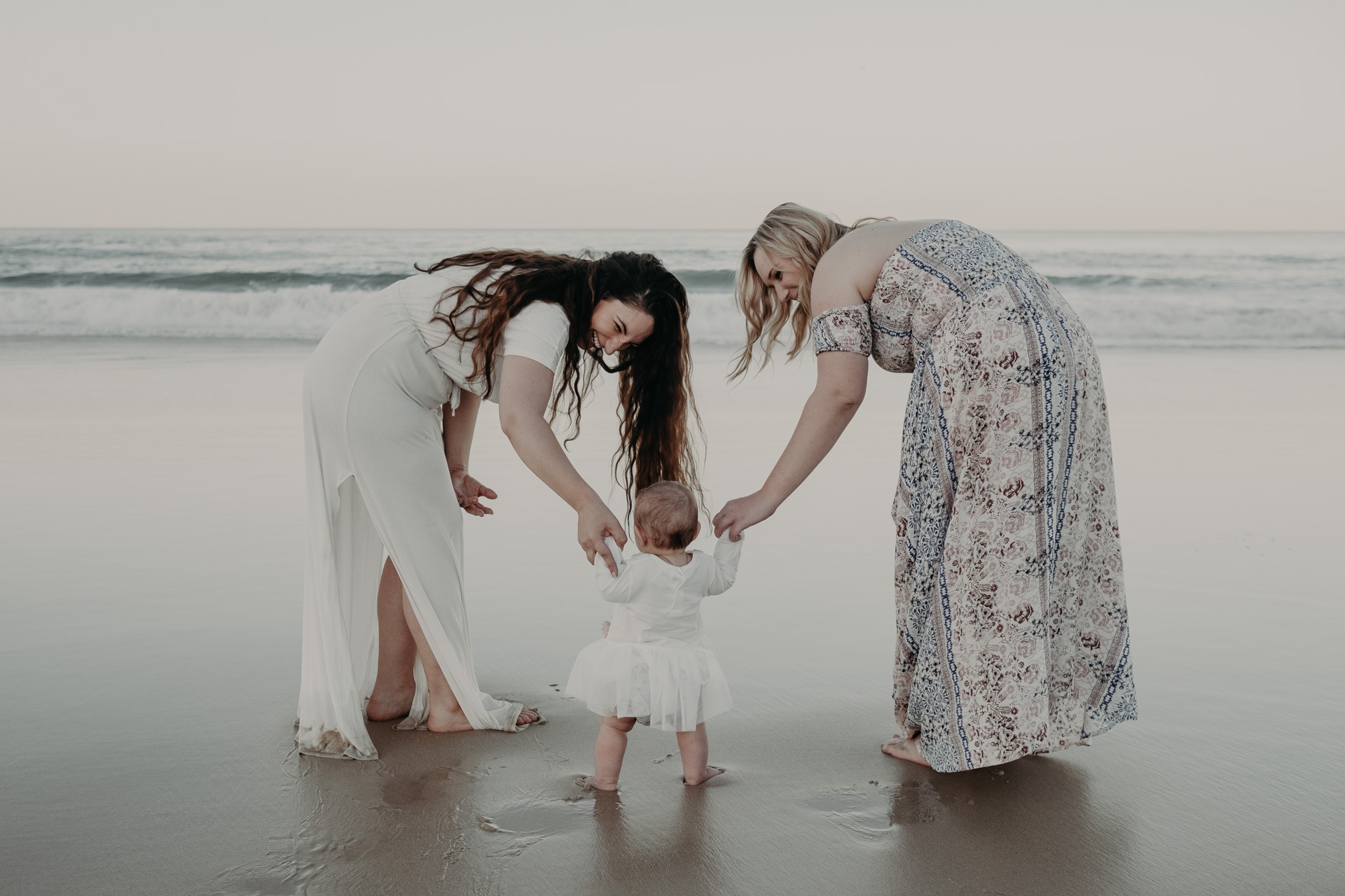 mother and baby on beach walking