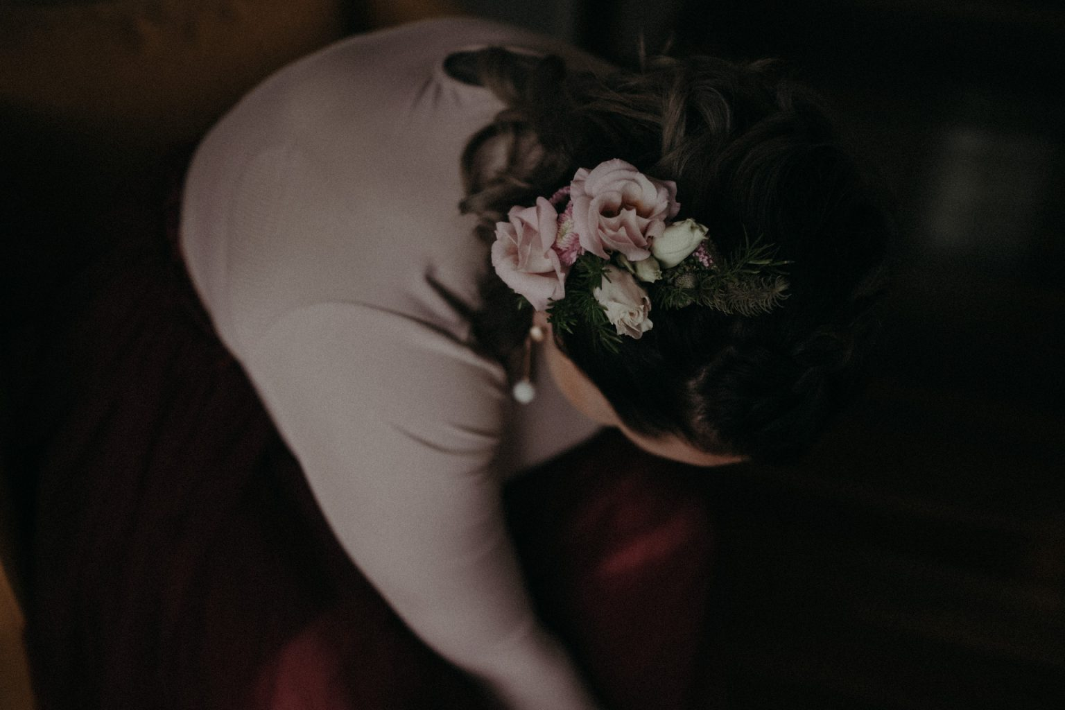 bride doing up shoes pink dress flowers