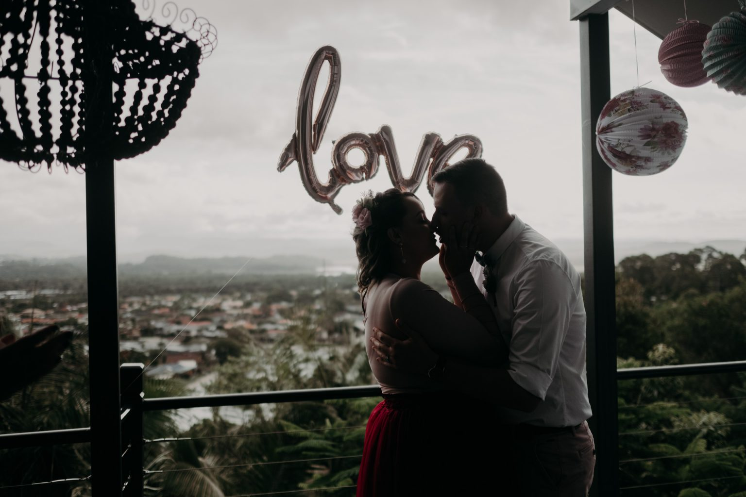 bride and groom on back deck private elopement kiss balloon