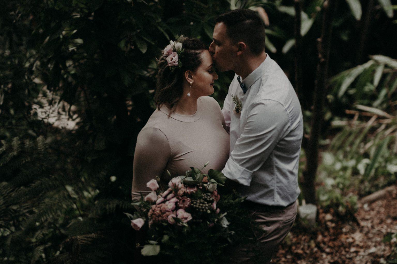 bride and groom in garden bouquet pink dress  kiss