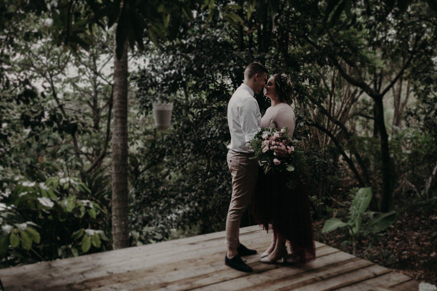 bride and groom in garden bouquet pink dress
