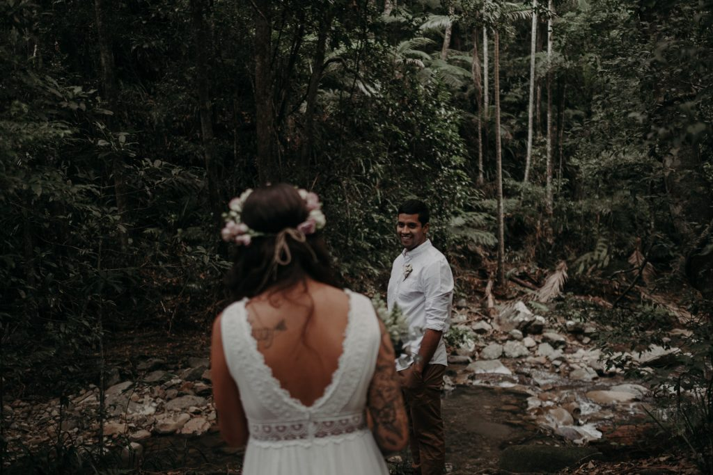 bride walking in forest alter elopement toward groom
