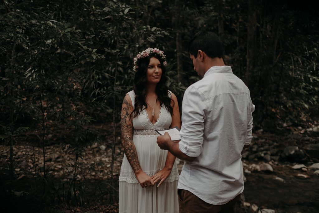 pregnant bride standing with groom in forest lace dress