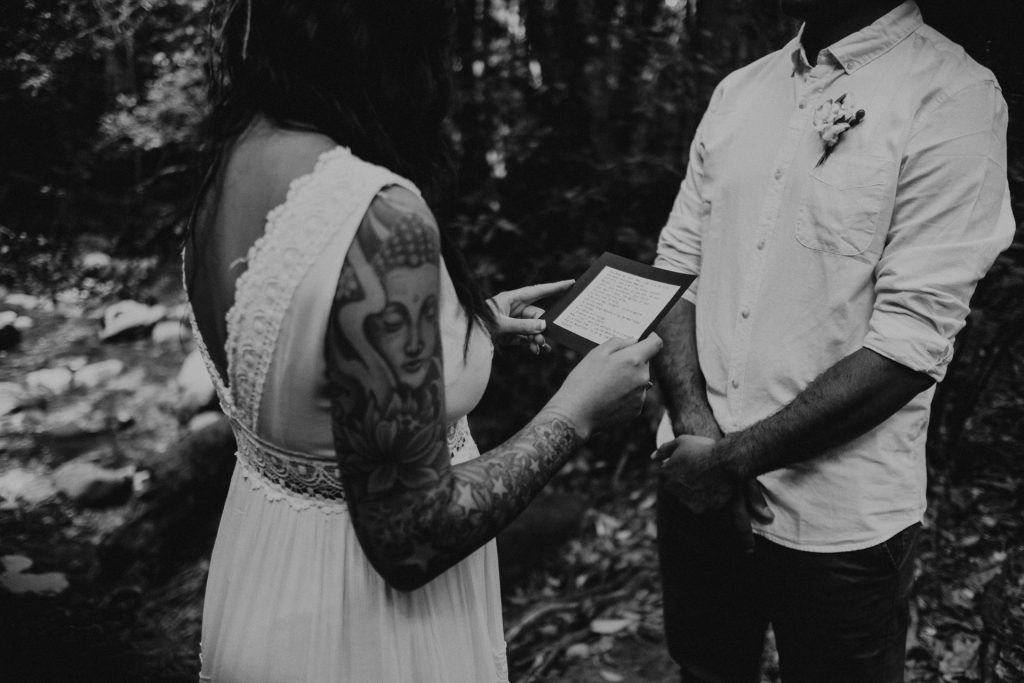pregnant bride standing with groom in forest lace dress reading vows