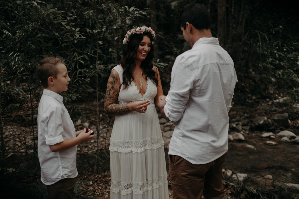 pregnant bride standing with groom in forest lace dress with ring