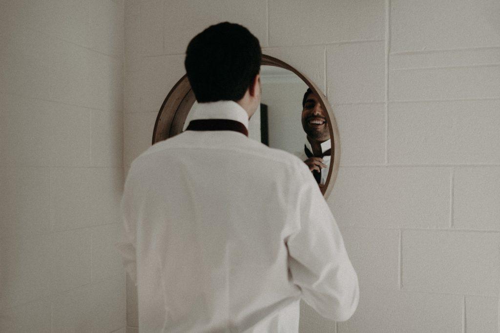 groom tying tie in mirror