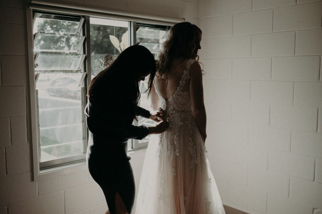 bridesmaid helping bride with dress window