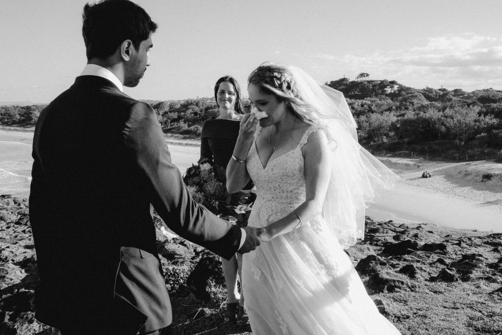 ceremony on windy cliff Fingal head bride in pink dress crying