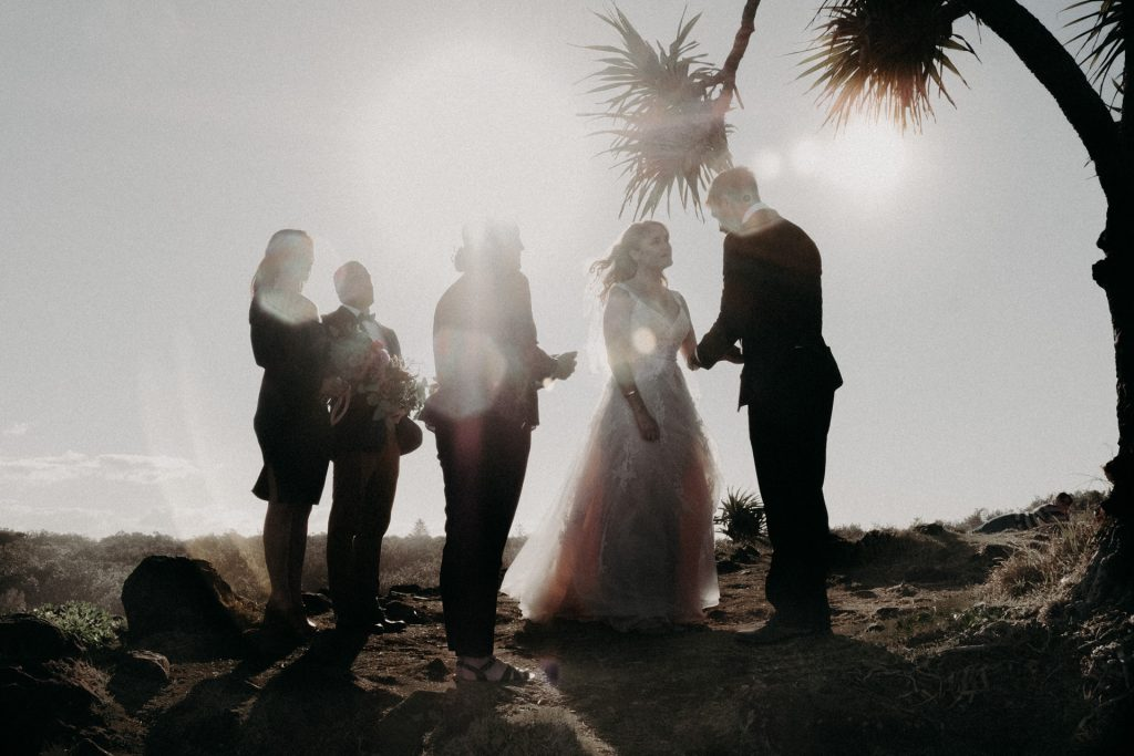 ceremony on windy cliff Fingal head bride in pink dress flare sun