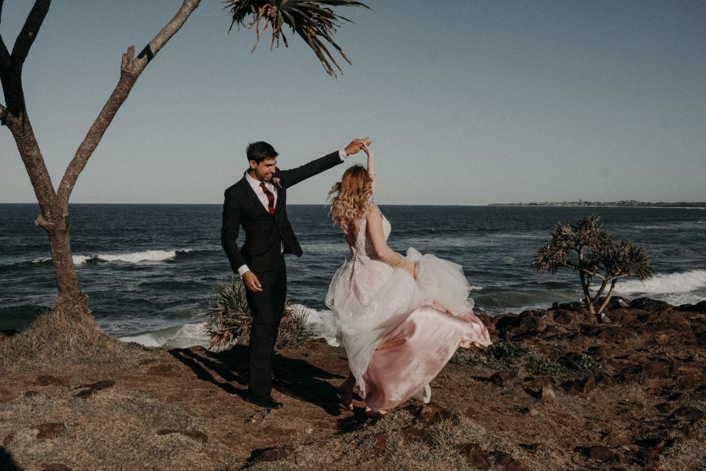 bride and groom dancing on clifftop