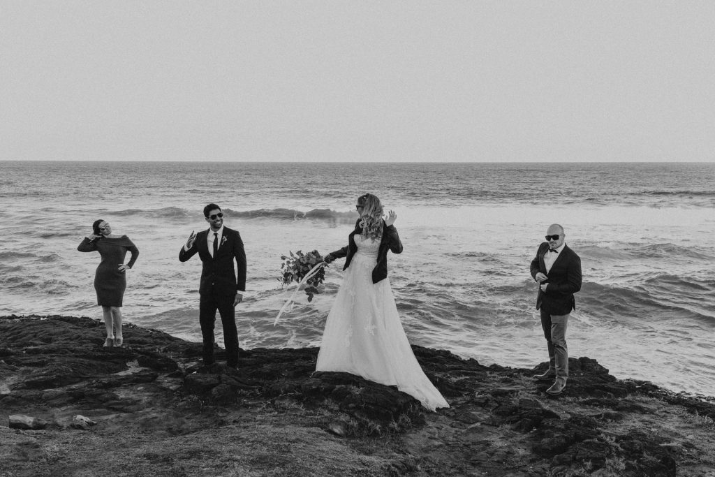 bride in dress and leather jacket standing on rocks with bridal party