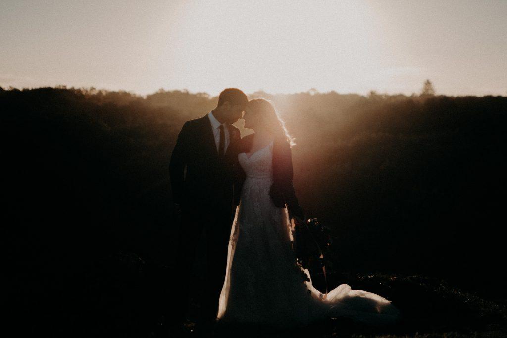 bride and groom in golden light on top of cliff elopement Fingal head