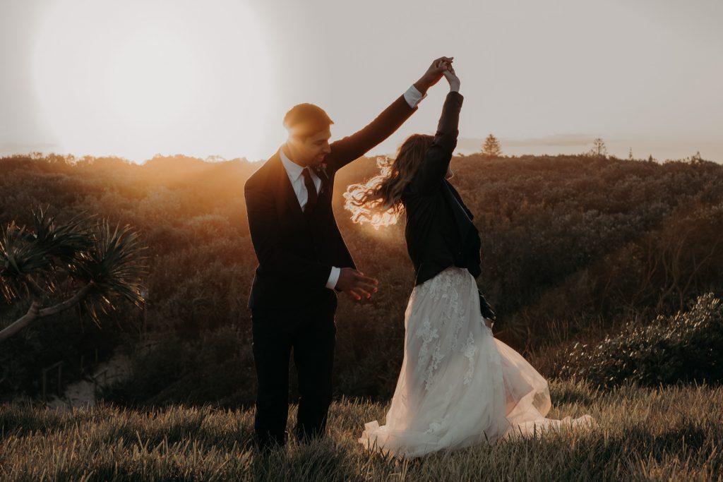 bride and groom dancing in golden light on top of cliff elopement