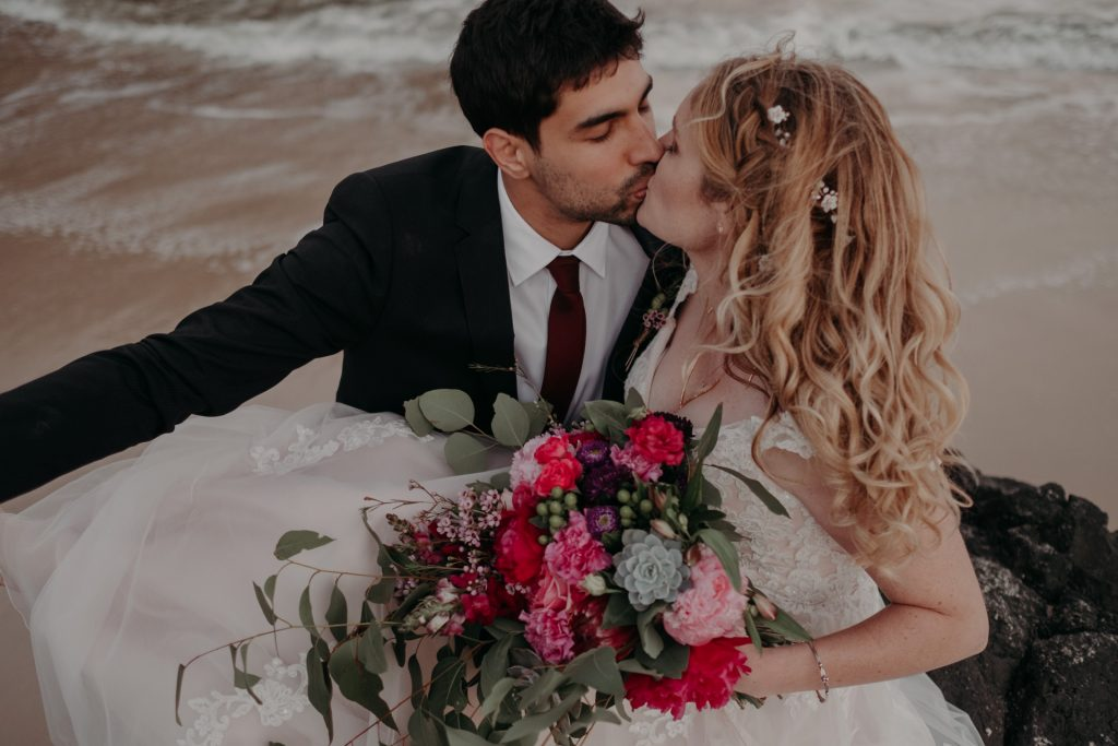 bride and groom kissing on beach pink flowers dress