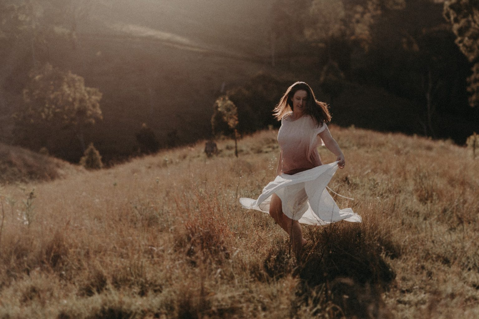 woman running in field with white skirt long grass