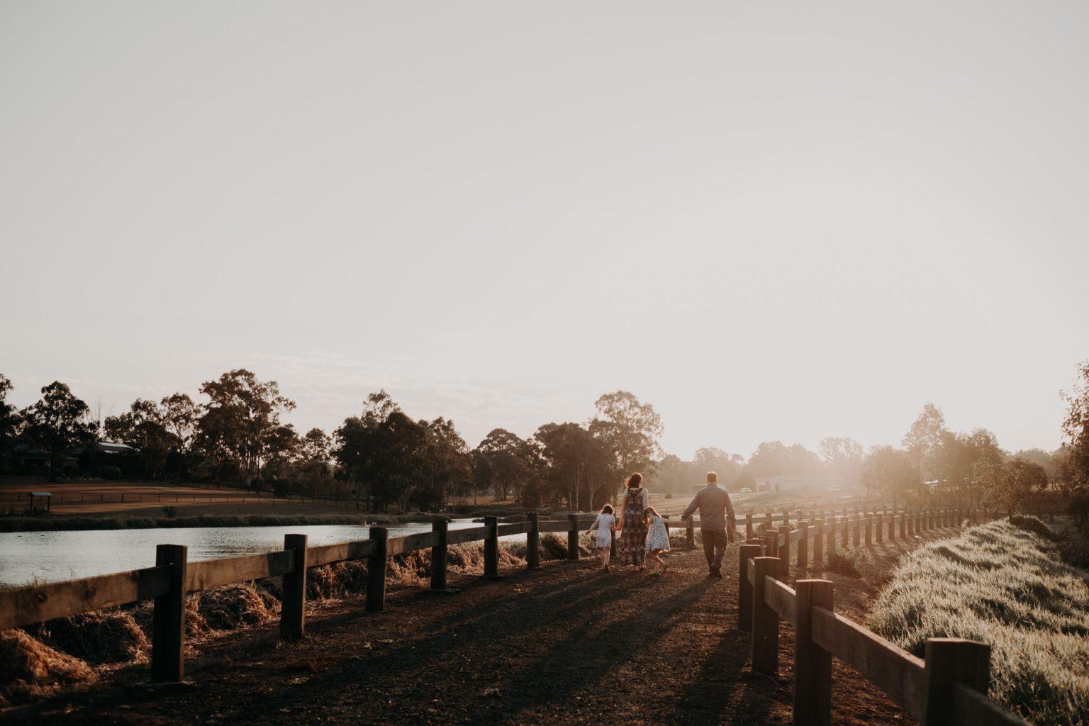 family walking in distance sunset golden light