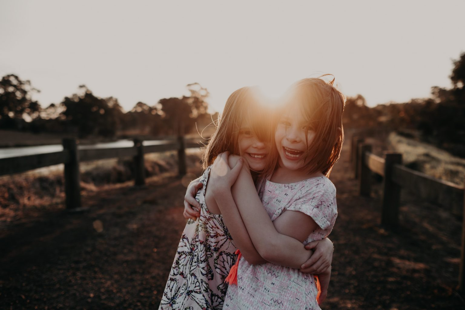 twin girls posing country lane golden light late afternoon sunset
