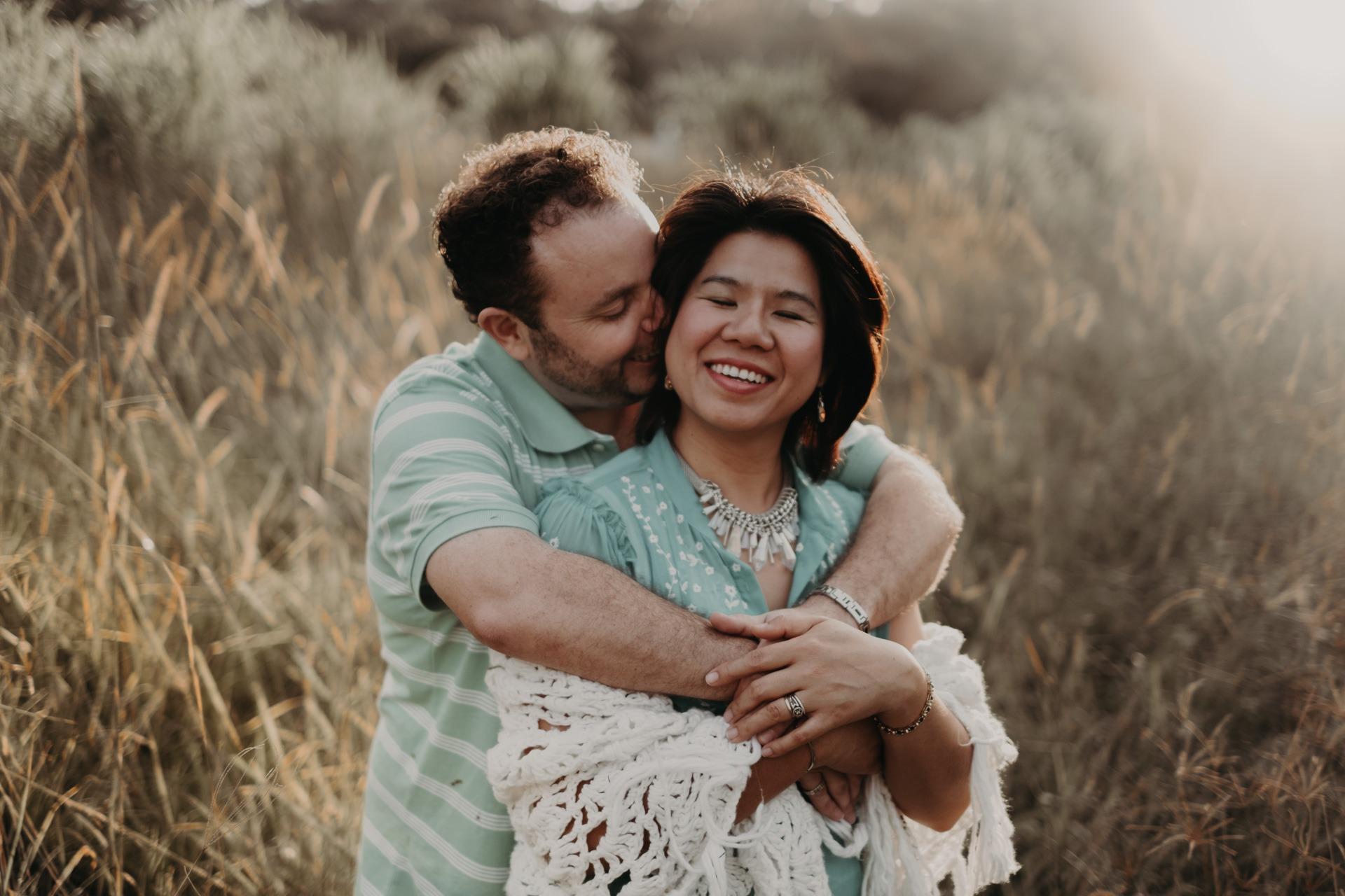 mum and dad hugging long grass mt tamborine family