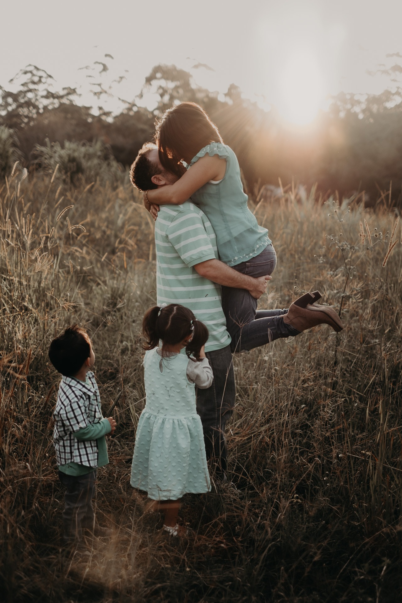 dad lifting mum up with kids looking on long grass mt tamborine family