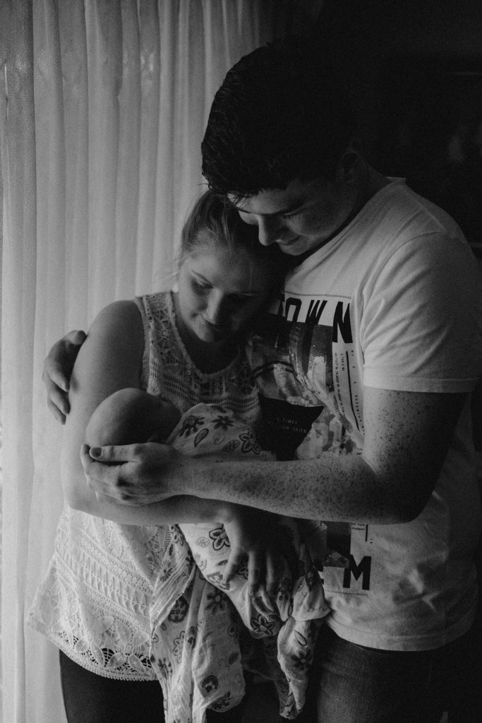 couple holding newborn shadow