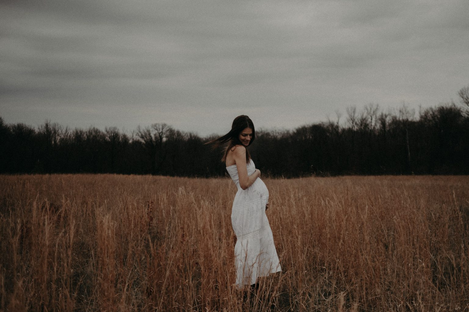 pregnant woman standing in field illinois
