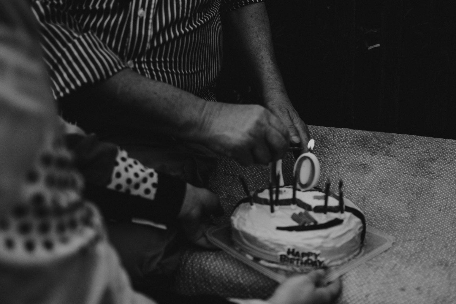 man lighting 70th birthday candles cake