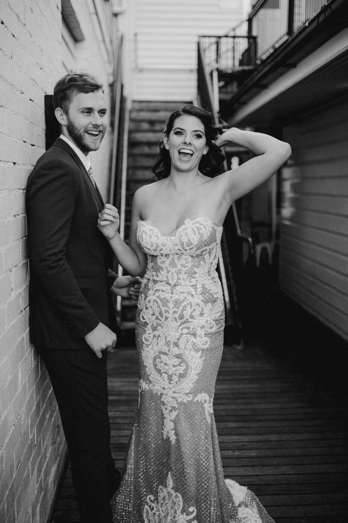 bride and groom laughing by wall at Alfred and constance bar fortitude valley brisbane sexy