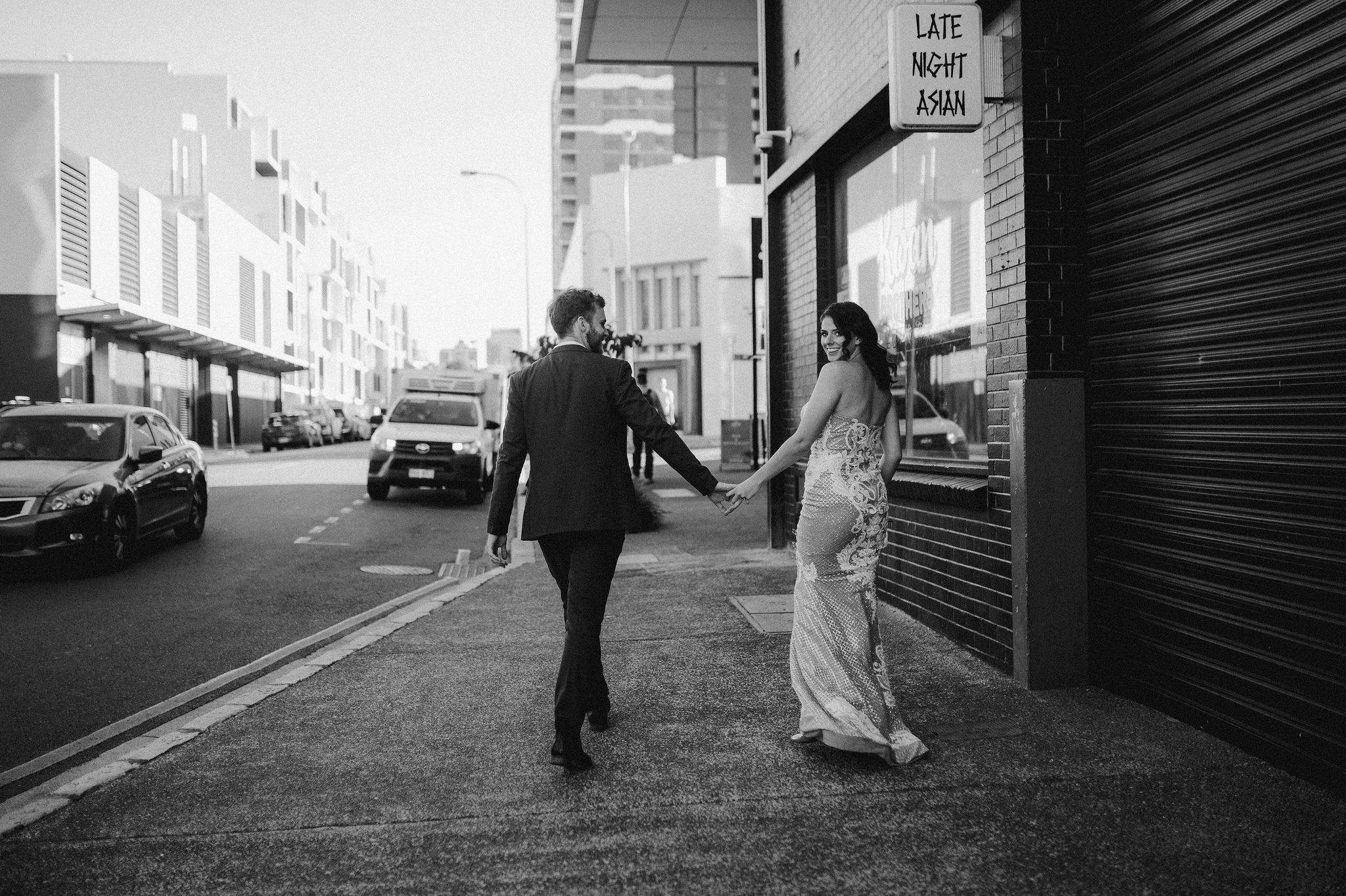 bride and groom walking through fortitude valley brisbane