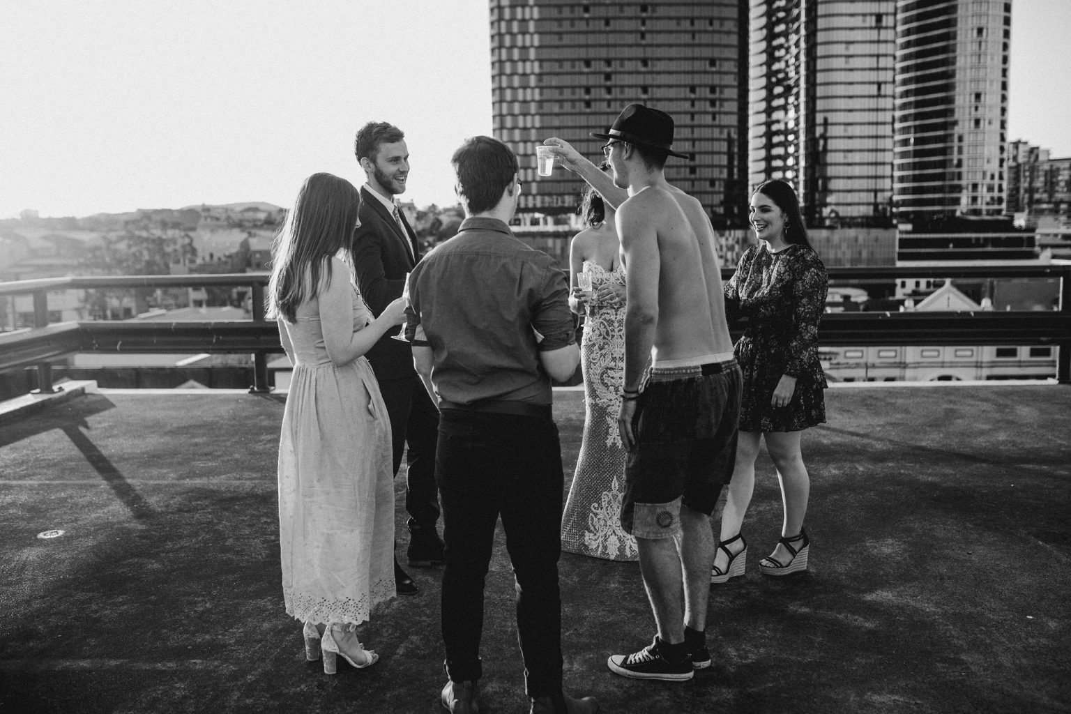 bride and groom drinking with bridal party on  rooftop for New York style elopement in Fortitude Valley Brisbane