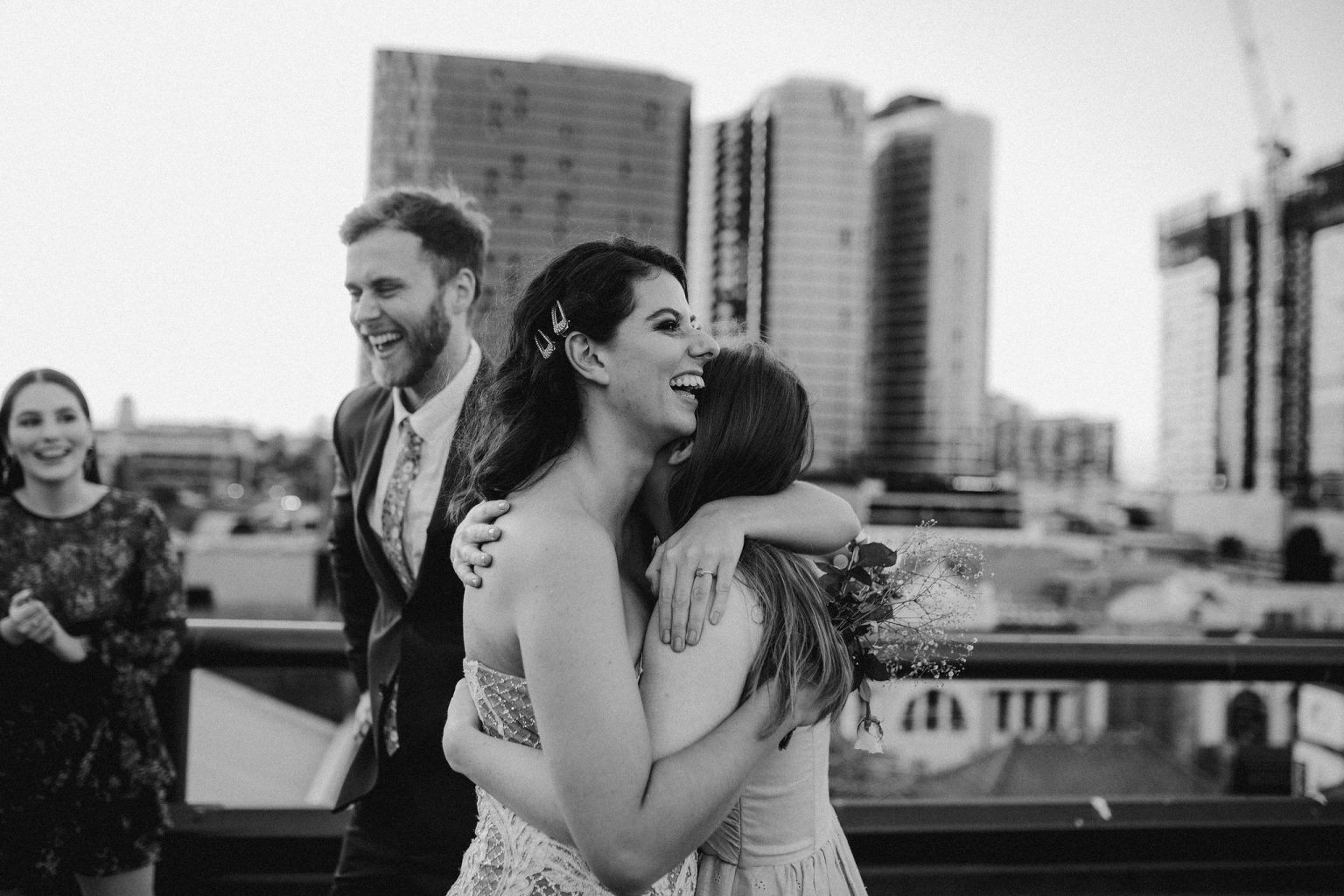 bride and groom hugging friends on  rooftop for New York style elopement in Fortitude Valley Brisbane