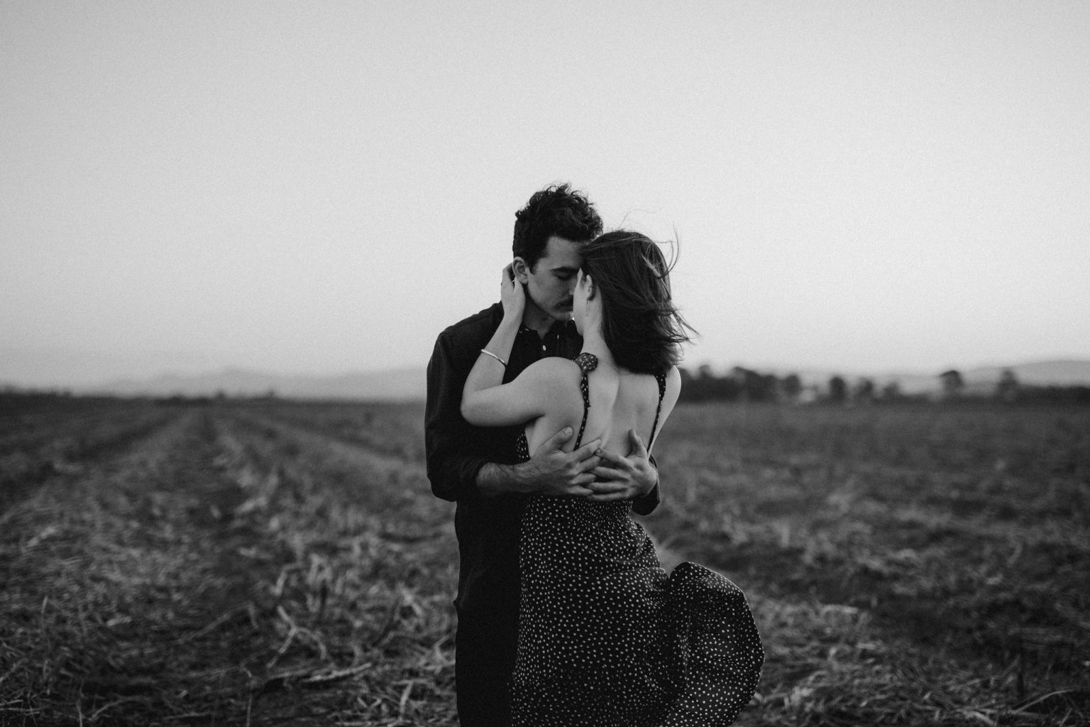 Man and woman hugging in field sexy