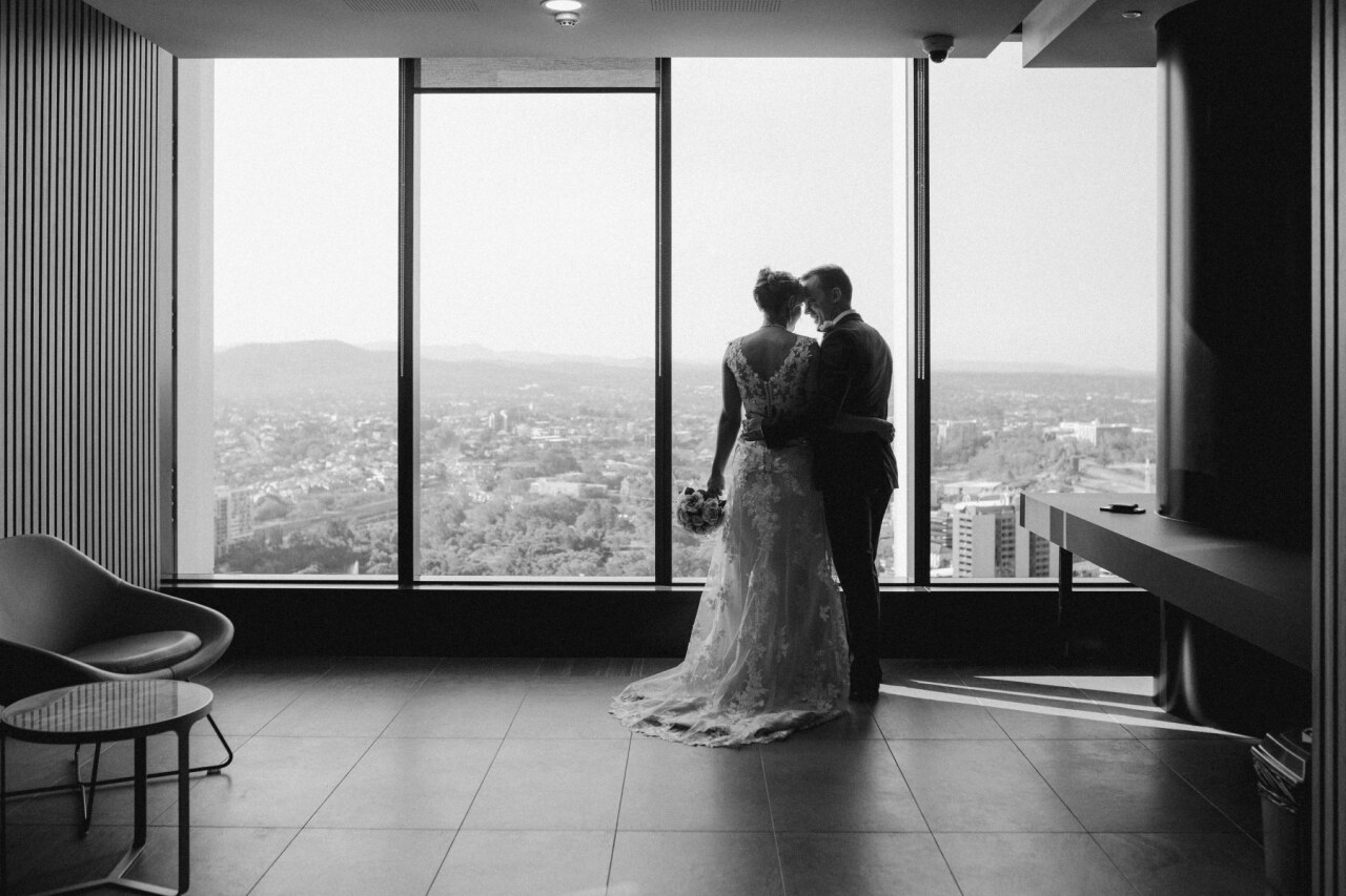 Bride and groom by window at at Brisbane Registry RBDM