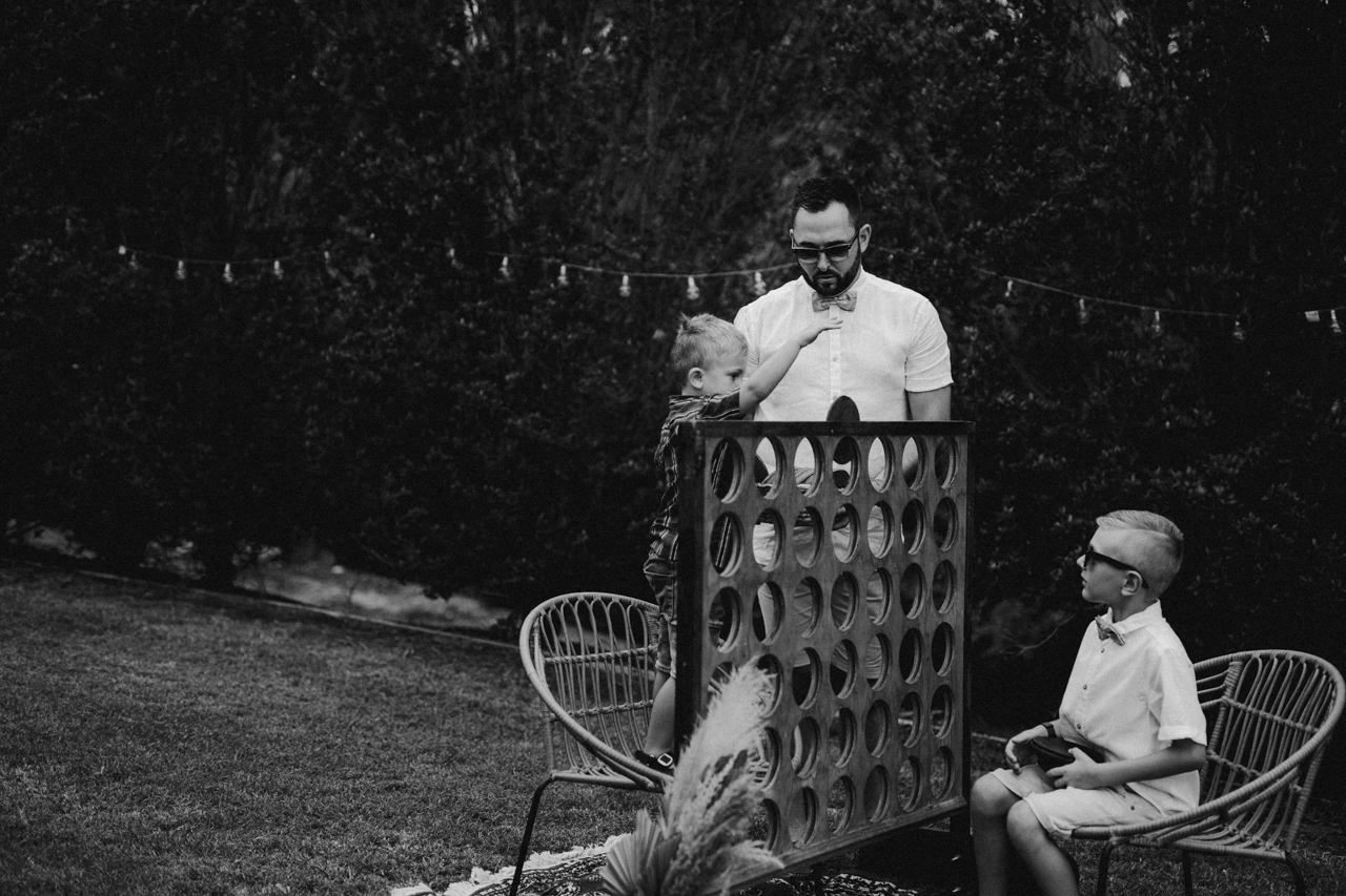groom and son playing garden connect four at garden wedding Eatons hill Brisbane