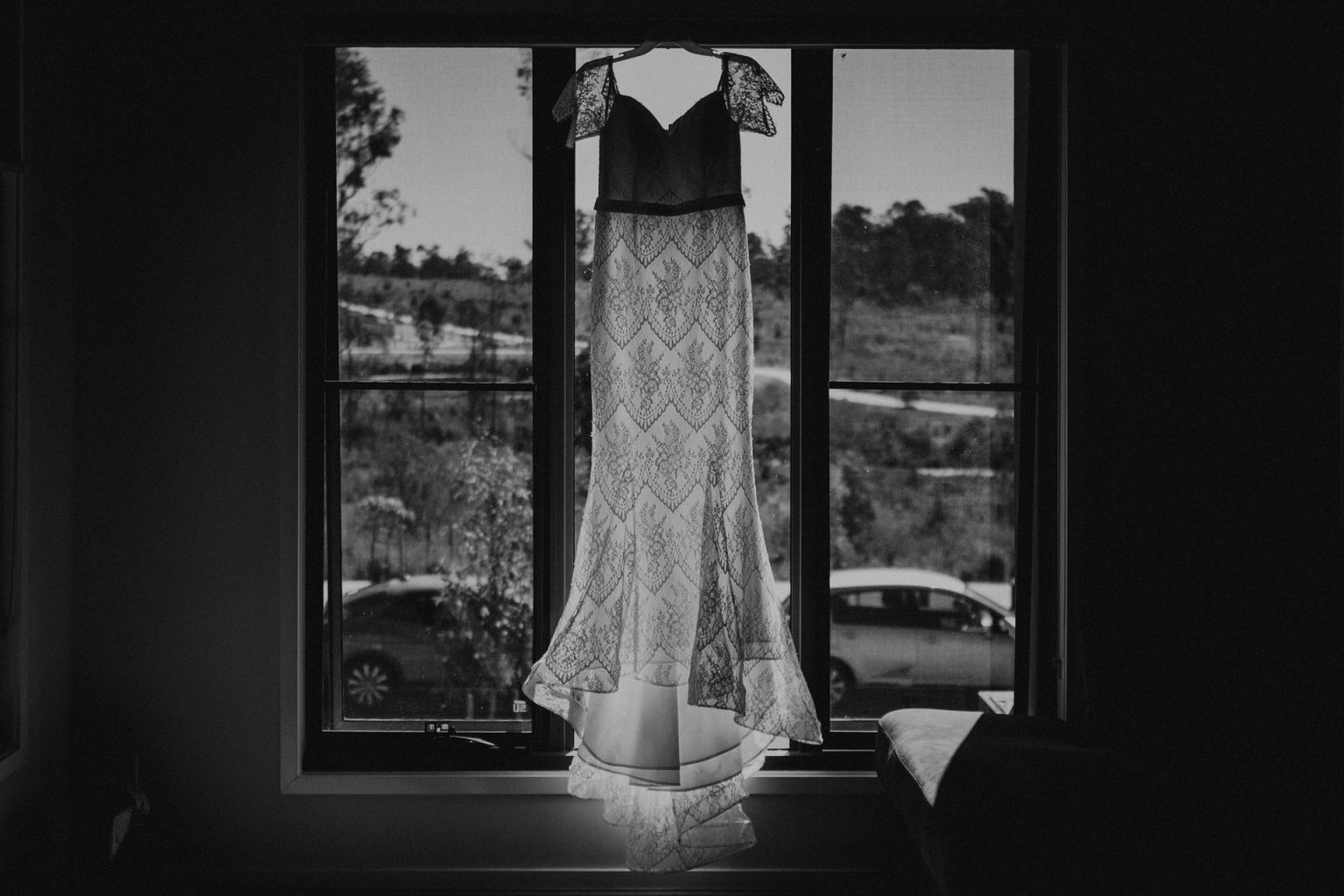 bridal gown hanging by window