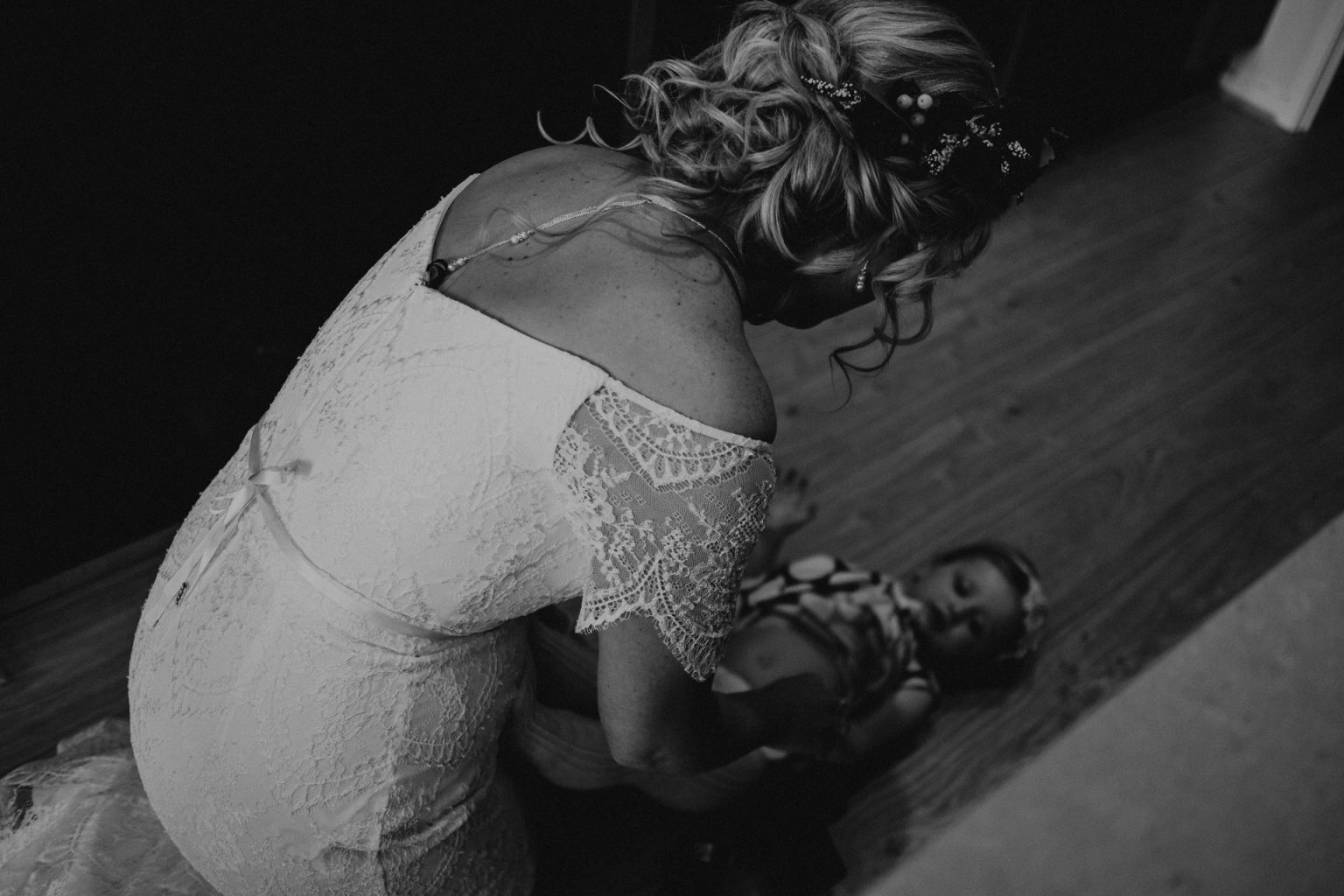 bride in dress changing nappy on floor