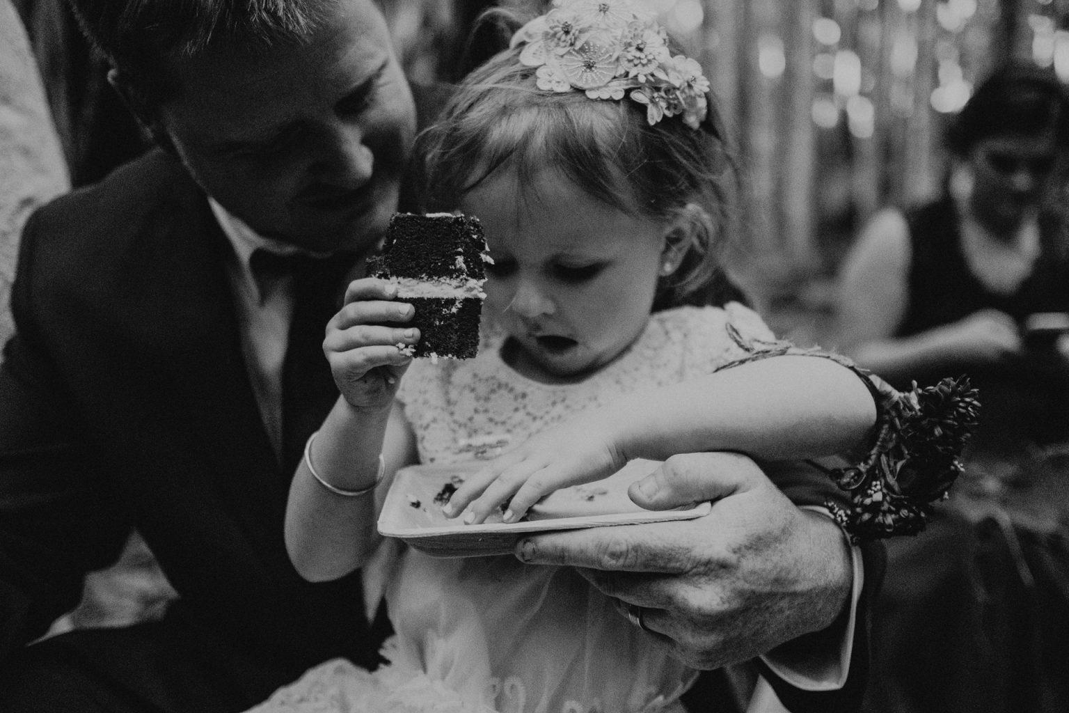 flower girl eats cake with groom